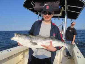 Marty WIsniewski with a beautiful striped bass which was his first ever keeper while fishing aboard RELENTLESS CHARTERS.